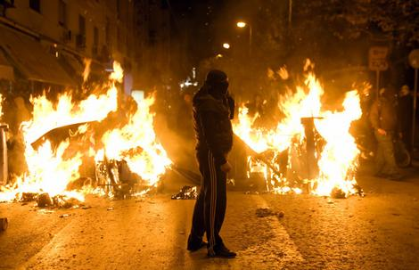 A rioter stands by a burning barricade in the center of Athens.