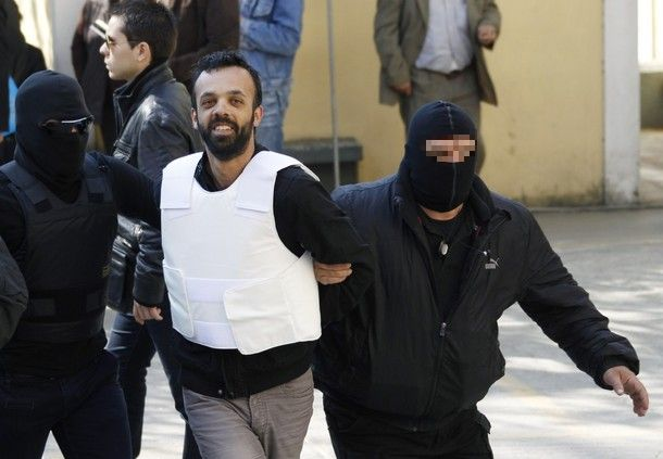 Greeks Kortesis is escorted by policemen to a prosecutor's office in Athens