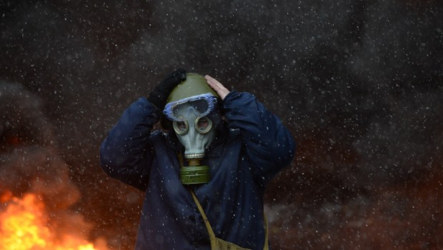 Protester_wearing_a_tear_gas_mask_against_background_of_the_massive_fire_set_by_protesters_to_prevent_internal_forces_from_crossing_the_barricade_line._Kyiv_Ukraine._Jan_22_2014-620x350