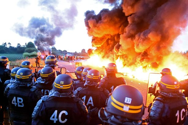 Riot-police-stand-guard-behind-a-fire-as-refinery-workers-hold-a-blockade-of-the-oil-depot-of-Douchy-Les-Mines