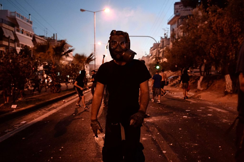 TOPSHOTS A potester wears a gas mask during clashes with police in the western Athens working class suburb of Keratsini on September 18, 2013, after a leftist musician was murdered by a suspected neo-Nazi. Pavlos Fyssas, a 34-year-old left-wing hip hop singer, was stabbed to death early today morning outside a Keratsini cafeteria.Police said a 45-year-old alleged member of the Golden Dawn neo-Nazi group arrested at the scene of the killing had confessed to stabbing Fyssas, who wrote music under the nickname Kilah P. Police fired tear gas at a small group of anti-fascism protesters who pelted them with wooden sticks and stones. AFP PHOTO / ARIS MESSINISARIS MESSINIS/AFP/Getty Images ORG XMIT: -