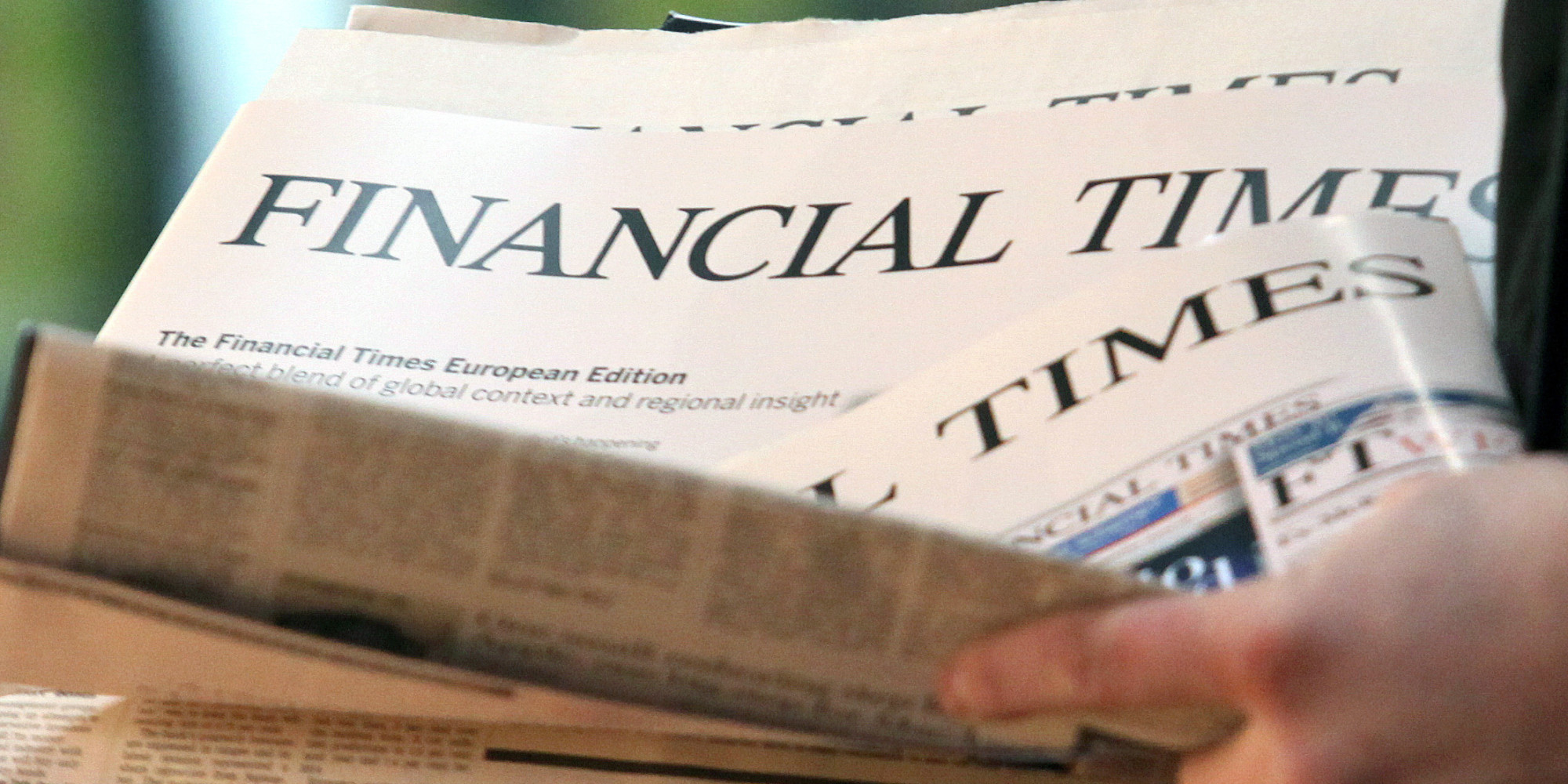 Copies of the English edition of the Financial Times are handed out at the central station in Hamburg,Germany, 07December 2012. After 13 years, the FTD sells its final issue. Photo: Bodo Marks
